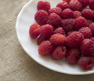 A scattering of fresh wild raspberries lying on a white plate. Close-up. Handful of fresh raspberries lying on a plate Stock Photo