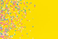Scattering multicolored confectionery topping dressing on yellow paper. Festive background. Copy space, Top view royalty free stock photos