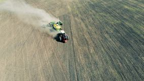 Aerial view of an agriculture tractor moving across field. Healthy Food Production Concept. Scattering truck in the middle of sowing process. 4K stock video footage