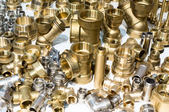 Scattering of various brass sanitary products. Abstract industrial background Stock Photography
