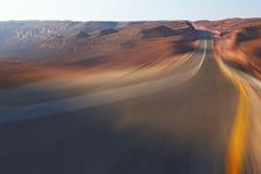 Scatti l'azionamento sull'alta velocità sulla strada principale in deserto Fotografie Stock