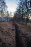 Scavatura della trincea Sterri, fossa di scavatura Fossa di terra lunga scavata per porre tubo o fibra ottica immagine stock