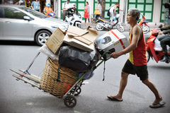Scavenger on a Bangkok Street. An unidentified scavenger transports discarded materials on August 23, 2012 in Bangkok, Thailand. Poverty remains major problem in Stock Image