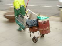 Scavenger cleans on the street. His working equipment carries on the carriage stock photography