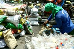Scavenger sorting through trash at a dump site in Manila, Philippines to look for recyclable things. A scavenger sorting through trash at a dump site in Manila Stock Photo