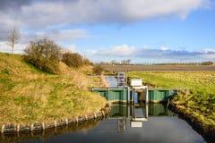 Scavi con una piccola diga in un'area olandese del ploder Fotografia Stock