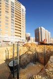 Scavi per la fognatura con acqua vicino alla costruzione in costruzione Immagini Stock