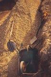 Scavo con materiali solidi dello scavo sotto la lastra del fondamento Costruzione, dolomia, pale e carriola fotografia stock