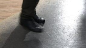 Scelga i pantaloni d'uso femminili del ballerino di rubinetto che mostrano i vari punti nello studio con il pavimento riflettente stock footage