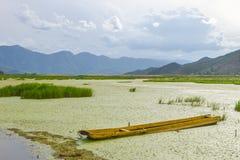 Scelga la barca abbandonata sul fiume di Lugu in Lijiang, il Yunnan, Cina immagine stock libera da diritti