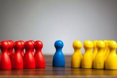 Scelga la figura blu del pegno fra i gruppi rossi e gialli immagini stock libere da diritti