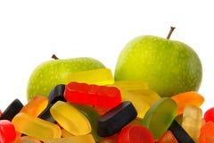 Scelga: mucchio della caramella o di due mele fotografia stock