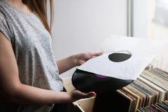 Scelta dei dischi di vinile retro nel negozio di musica Immagine Stock
