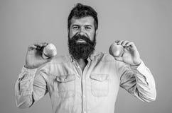 Scelta nutrizionale L'uomo con la mela della tenuta dei pantaloni a vita bassa della barba fruttifica a disposizione Fatti di nut fotografia stock libera da diritti