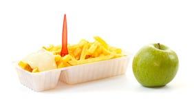 Scelta una mela sana o della porzione non sana di patate fritte Fotografia Stock