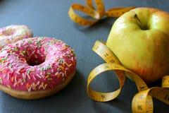 Scelte sane dell'alimento della mela e della ciambella sul bordo di legno immagini stock