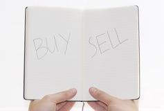 Scelte vendita/compri sul blocchetto per appunti, priorità bassa bianca. Fotografia Stock