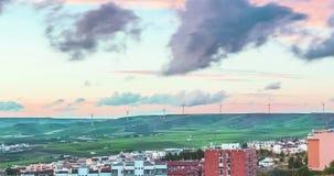 Scena al rallentatore con la città, le colline e l'energia rinnovabile alternativa del generatore eolico nel fondo, dal tramonto  archivi video