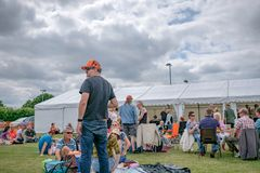 Scena all'aperto di un festival di musica in diretta che mostra i gruppi di famiglie fuori di grande tenda foranea nell'estate fotografie stock