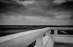 Scena in bianco e nero della spiaggia del fango alla marea con il cielo e le nuvole grigi Vista di prospettiva dal ponte concreto fotografia stock libera da diritti
