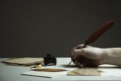 Scena con una mano del ` s dell'uomo che scrive una lettera o una storia con l'annata q Fotografie Stock Libere da Diritti
