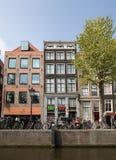 Scena del canale con biciclette, caffè del marciapiede e case olandesi tradizionali a Amsterdam netherlands fotografia stock