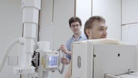 Scena dell'attrezzatura della radiografia in clinica con l'uomo in rontgen macchina stock footage