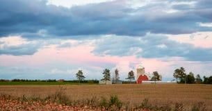 Scena dell'azienda agricola familiare con il cielo drammatico a penombra Fotografie Stock Libere da Diritti