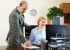 Scena dell'ufficio con due anziani ed i lavoratori seri Immagini Stock Libere da Diritti