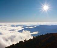 Scena della montagna con il sole sopra le nubi Immagini Stock Libere da Diritti