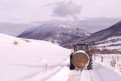 Scena della montagna di inverno con l'agricoltore sul trattore. Immagine Stock