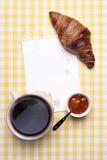 Scena della prima colazione con caffè, il croissant, l'inceppamento e la carta in bianco Fotografie Stock