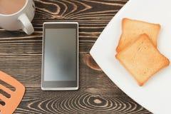 Scena della prima colazione con pane tostato, telefono, tazza sulla tavola di legno Immagini Stock Libere da Diritti