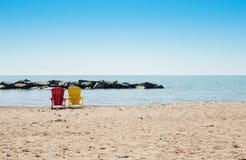 Scena della spiaggia con due sedie variopinte del adirondack fotografia stock libera da diritti