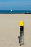 Scena della spiaggia con la barca a vela ed il cielo blu Fotografia Stock