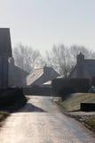 Scena della via del villaggio di inverno - sole sulla strada ghiacciata Immagini Stock