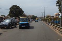 Scena della via nella città della Bissau con i bus pubblici Toca Toca in un viale vicino al mercato di Bandim, in Guinea-Bissau immagine stock