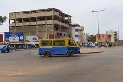 Scena della via nella città della Bissau con un toca-toca del bus in una rotonda vicino al mercato di Bandim, in Guinea-Bissau, fotografia stock libera da diritti