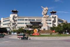 Scena della via nella città di Dunhuang, con una rotonda con una statua di un Apsara che gioca un pipa ed il partito comunista ci fotografie stock