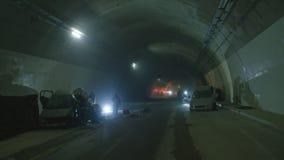 Scena dentro un tunnel, pompieri di incidente stradale che salvano la gente dalle automobili stock footage