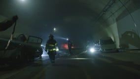 Scena dentro un tunnel, pompieri di incidente stradale che salvano la gente dalle automobili video d archivio