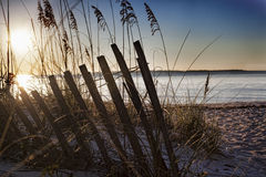 Scena di alba alla spiaggia sulla baia immagini stock