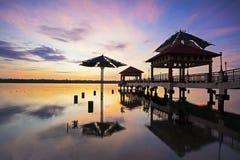 Scena di alba con il ponte della siluetta nel mare Immagini Stock