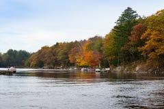 Scena di caduta con le barche e gli alberi variopinti Fotografia Stock