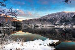 Scena di inverno con le montagne ed alberi di Snowy, nuvole variopinte e riflessione del lago al tramonto fotografia stock