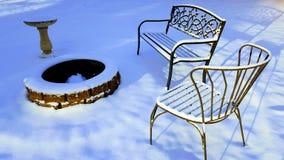 Scena di inverno, pozzo del fuoco, vaschetta per i uccelli, sedie del metallo nella neve Immagine Stock Libera da Diritti