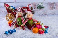 Scena di Natale con gli elfi, i calzini di Natale, i mandarini ed il regalo Immagini Stock Libere da Diritti