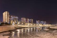 Scena di notte con il canale vicino congelato delle costruzioni di appartamento, Chang-Chun, Cina Fotografia Stock