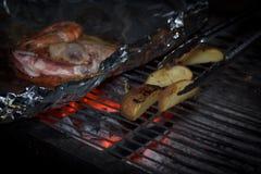 Scena di notte di cottura patata e dei frutti di mare in stagnola sulla griglia Immagini Stock