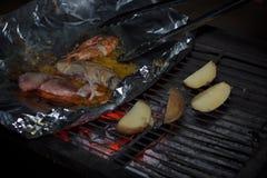 Scena di notte di cottura patata e dei frutti di mare in stagnola sulla griglia Fotografia Stock